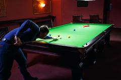 Playing pool, man aiming the billiard ball Stock Photos