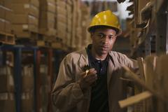 Black man with walkie-talkie working in warehouse Kuvituskuvat