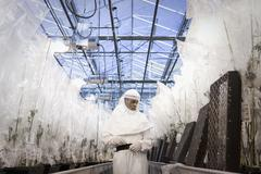 Scientist in clean suit working in greenhouse Kuvituskuvat