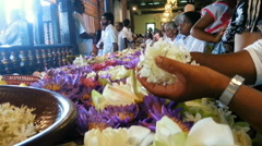 Religious people bringing lotus flower offerings and praying in Buddhist temple Stock Footage