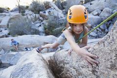 Mixed race girl rock climbing Stock Photos