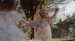 Two children in fairy costumes twirling in trees Stock Footage