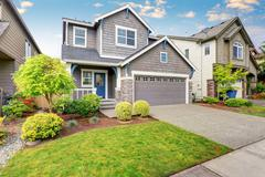Nice curb appeal of two level house, mocha exterior paint and driveway - stock photo