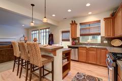 View of kitchen interior with hardwood storage combination, bar and pendant l - stock photo