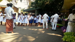Schoolchildren in white uniforms bring lotus flower offerings to Buddhist temple Stock Footage