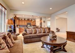 Classic brown and white living room interior with carpet floor. View of kitch - stock photo