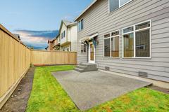 House exterior with mocha siding. View of patio area with concrete floor. Fen Stock Photos