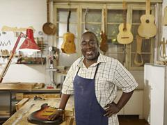 Black craftsman in guitar workshop Stock Photos