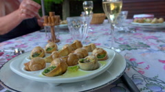 French table - Cooked snails, escargot in a plate - summer outdoor dinner Stock Footage