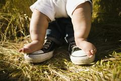 Baby's feet on top of father's feet Stock Photos
