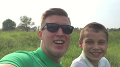 Happy father and son playing, pictures of yourself to use smartphone, slow mo Stock Footage