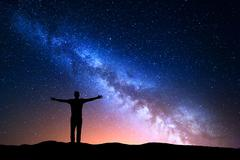 Night landscape with Milky Way. Silhouette of a standing young man - stock photo