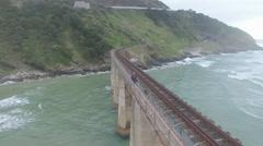 Girl Walking Across Ocean Bridge Aerial Revolving Shot Stock Footage