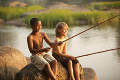 Smiling boys fishing together Stock Photos