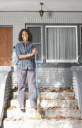 Black woman sweeping front stoop steps Stock Photos