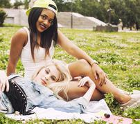 two young pretty teenager girls best friends laying on grass making selfie photo - stock photo