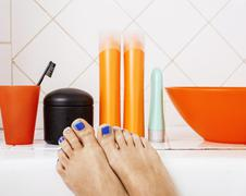 Woman legs in bathroom with lot of stylish stuff for care, pedicure creative Stock Photos