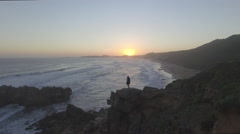 Aerial of Girl Standing on Ocean Rock at Sunset Stock Footage