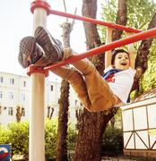 little cute blond boy hanging on playground outside, alone training with fun - stock photo
