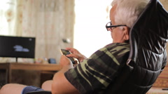 Senior man sitting with a phone in a leather chair near the house TV. Man typing Stock Footage