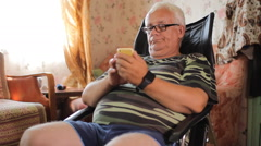 Senior man sitting with a phone in a leather chair at home. Man typing sms and Stock Footage
