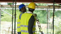 4K Builders working at construction site with female architect looking at plans Stock Footage