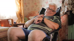 Senior man sits with smart clock in a leather chair near the house TV. A man Stock Footage