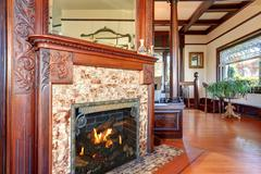 Clouse up view of antique fireplace with decorative tile trim and mirror in b Stock Photos