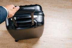 Men's shoes suitcase and bag lay on the laminate at home Stock Photos