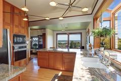 Great kitchen room with granite counter tops, built-in appliances, pendant li - stock photo