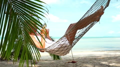 Young woman lying in a hammock on the beach with phone Stock Footage