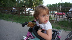 Little funny child rides a bicycle, smile, urban green park, nature. Stock Footage