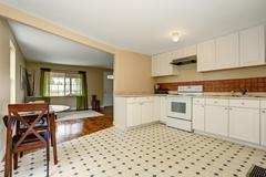White kitchen room interior with tile floor and dining table set. The room is Stock Photos