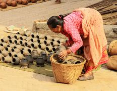 Nepali woman dries the clay vases. Bhaktapur, Nepal on April 03, 2014 Stock Photos