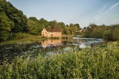 Early morning landscape across River to old water Mill - stock photo