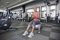 African American woman text messaging on cell phone in health club Kuvituskuvat