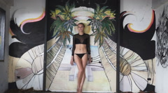 Sexy blonde woman wearing a black elegant swimsuit and earrings dancing. - stock footage