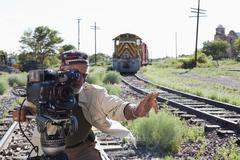 African American man with film camera near railroad tracks Stock Photos