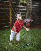 African American baby playing in sprinkler Stock Photos