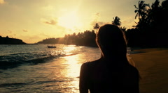 Female silhouette at sunset, woman standing on beach and watching sun going down Stock Footage