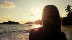 Lonely girl watching sunset on tropical beach, stormy ocean waves coming ashore Stock Footage