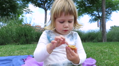 Baby eating cupcake in park Stock Footage