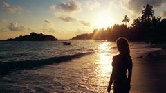 Strong independent woman standing in ocean water at sunset, enjoying freedom - stock footage
