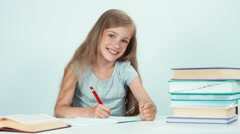 Close up portrait schoolgirl something writing in her school notebook on white Stock Footage