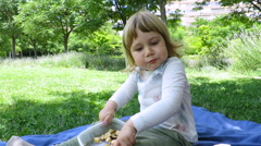 Baby eating sitting in park Stock Footage