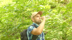 Tourist man close-up walking through the forest drinks water. man with backpa Stock Footage