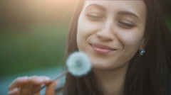 Smiling Woman Blowing on a Dandelion Stock Footage