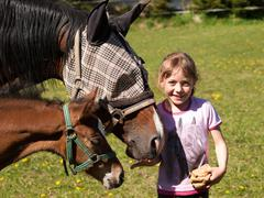Portrait of girl feeding mare and foal with bread Stock Photos
