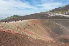 Tourists walking around Silvestri crater of Mount Etna, Italy - stock photo