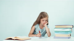 Schoolgirl writing in her notebook. Child girl sitting at the table on white Arkistovideo
